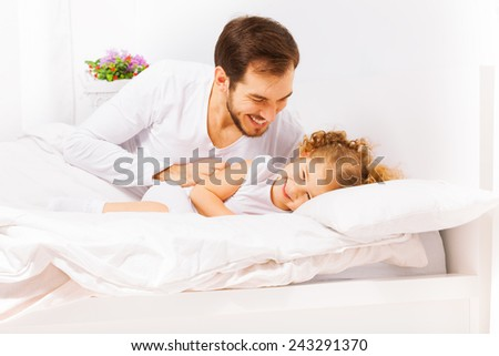 Happy father with cute small daughter playing