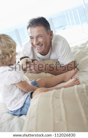 Happy father with daughter in bed at home