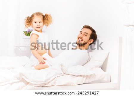 Happy father with his daughter in white pajamas