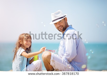 Happy father with his daughter making soap bubbles during summer vacation - stock photo