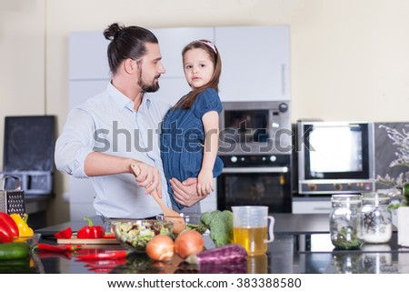 happy father with his little daughter  preparing food in their kitchen - stock photo