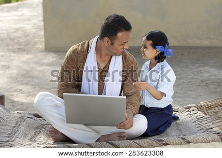 Happy father with his little daughter using laptop - stock photo