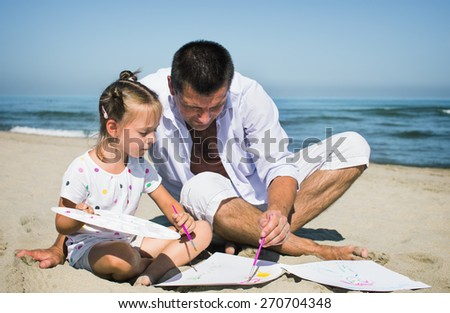 happy father with his small daughter painting on the seaside