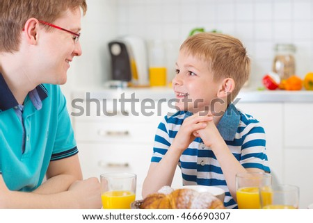 Happy father with his son talking during breakfast in kitchen