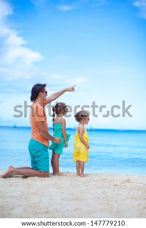 Happy father with his two daughters sitting on tropical beach vacation