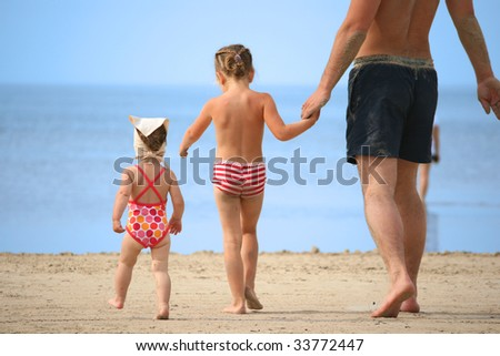 happy father with his two young daughters at seaside