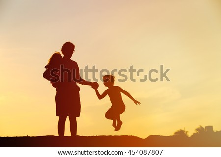 happy father with son and daughter jumping at sunset