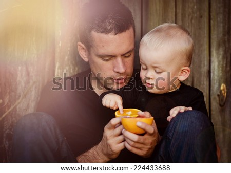 Happy father with son eating orange and by the wooden fence - stock photo
