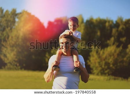 Happy father with son having fun outdoors, sunny summer day, warm sunlight on the sunset - stock photo