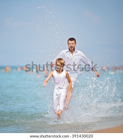 Happy father with son playing together, running and jumping on a beach on a sunny hot summer day - stock photo