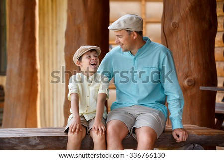 Happy father with son talking and having rest outdoors in city on beautiful summer day - stock photo