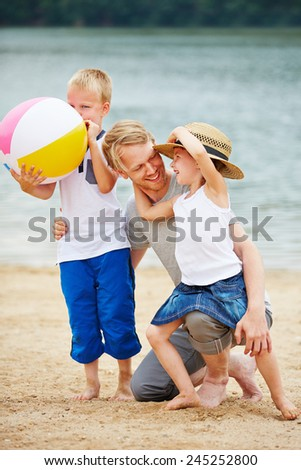 Happy father with two children on vacation on a beach at a sea