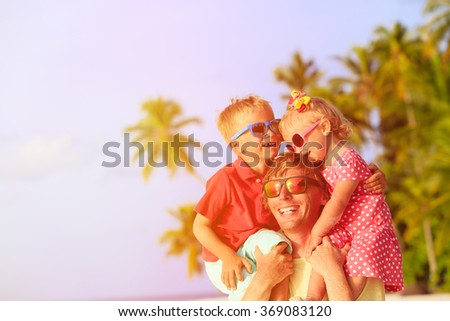 happy father with two kids on shoulders having fun at beach - stock photo