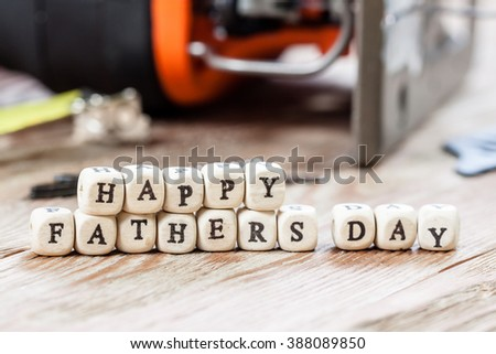 Happy Fathers Day blocks on a rustic wood background. Work tools concept.