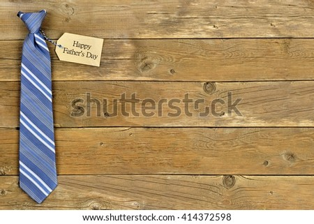 Happy Fathers Day gift tag with blue striped necktie on rustic wood background - stock photo