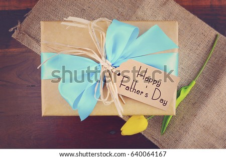 Happy Fathers Day natural kraft paper wrapped gift owith pale blue ribbon on dark wood background, with applied filters.