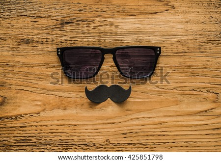 Happy fathers day sticker, wooden glasses, black paper mustache on wooden background