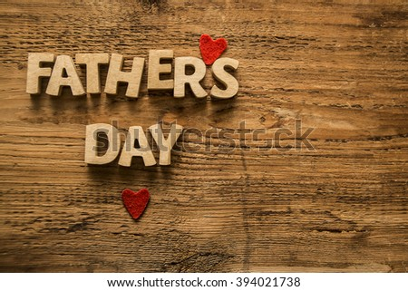 Happy Fathers Day wooden letters on a rustic wood background. empty space for inscription or objects. two red heart - stock photo