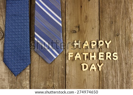Happy Fathers Day wooden letters on a rustic wooden background with blue ties - stock photo