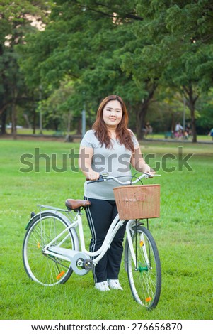 Happy fatty asian woman posing with bicycle outdoor in a park - stock photo