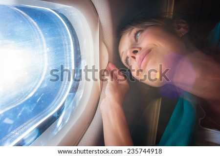 Happy, female airplane passanger enjoying the view from the cabin window over the blue sky (shallow DOF; intentional flare) - stock photo