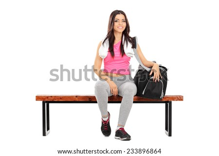 Happy female athlete sitting on a wooden bench isolated on white background - stock photo