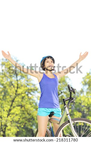 Happy female biker posing with raised hands on a mountain bike outdoors - stock photo