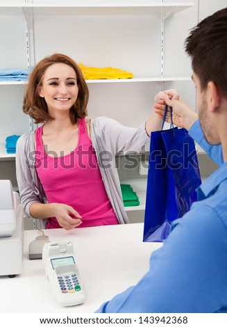 Happy Female Cahier Handing Over Shopping Bag To Customer - stock photo