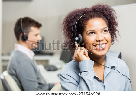 Happy female call center agent using headset with male colleague in office - stock photo