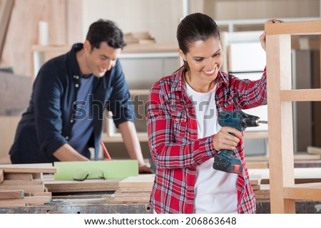 Happy female carpenter drilling wood while colleague working in background at workshop - stock photo