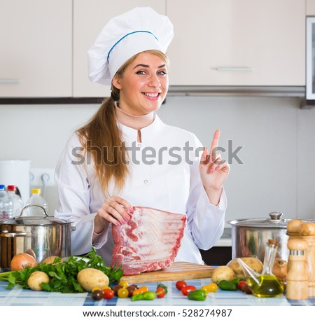 Happy female chef posing with pork ribs in domestic kitchen