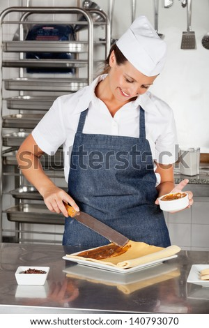 Happy female chef preparing chocolate roll in industrial kitchen - stock photo