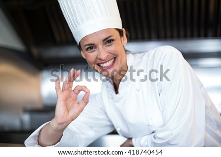 Happy female chef showing ok sign while standing in commercial kitchen - stock photo