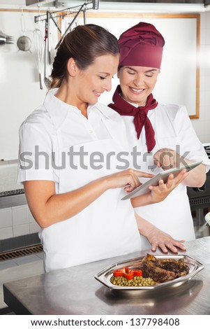 Happy female chefs looking for recipe on a digital tablet while cooking at kitchen - stock photo
