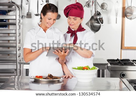 Happy female chefs with digital tablet discussing in commercial kitchen - stock photo