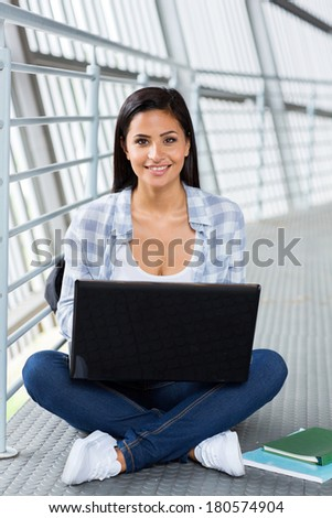 happy female college student using laptop - stock photo