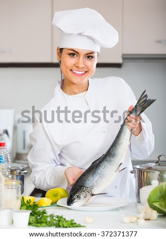 Happy female cook preparing big fish in restaurant
