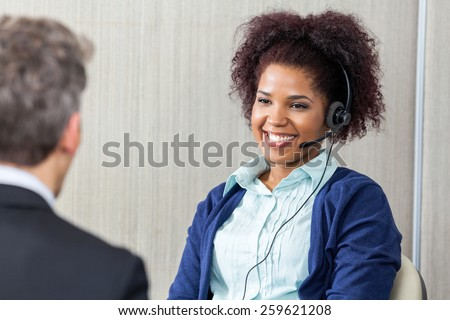 Happy female customer service agent wearing headset looking at manager in office - stock photo