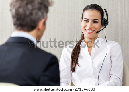 Happy female customer service representative wearing headset while looking at manager in office - stock photo