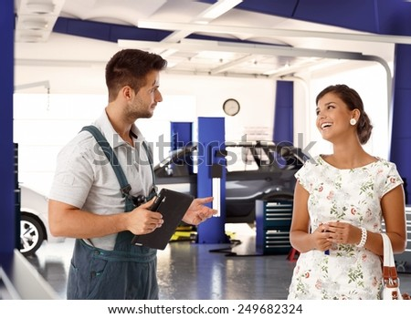 Happy female customer talking to car mechanic in auto repair shop, smiling happy. - stock photo