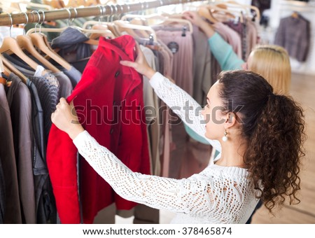 Happy female customers selecting coats and jackets at the shop - stock photo