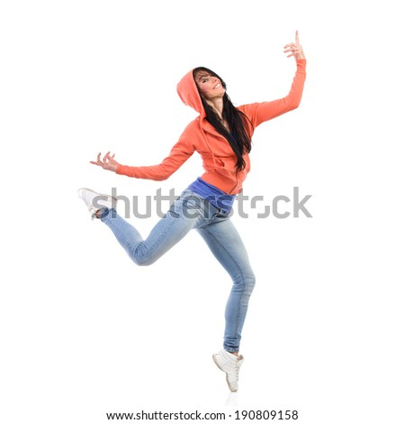Happy female dancer standing on one leg with arms outstretched. Full length studio shot isolated on white.