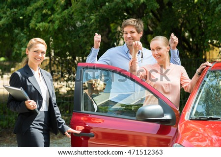 Happy Female Dealer Standing Besides Couple Showing Key Of Newly Purchased Car
