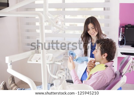 Happy female dentist showing x-rays to a patient - stock photo