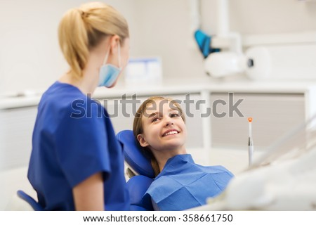happy female dentist with patient girl at clinic