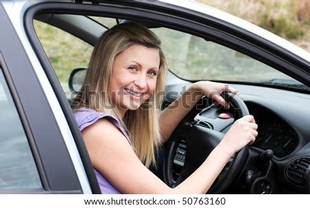 Happy female driver at the wheel sitting in her car smiling at the camera - stock photo