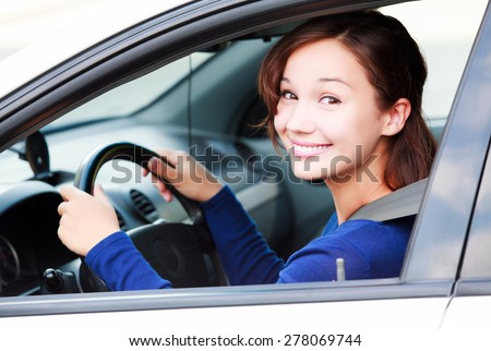 Happy female driver smiling to you