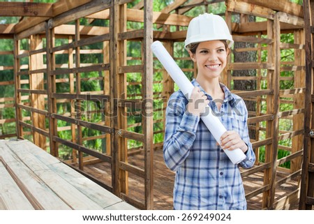Happy female engineer looking away while holding blueprint in incomplete timber cabin at construction site - stock photo