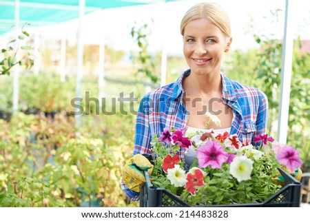 Happy female farmer with flowers looking at camera - stock photo