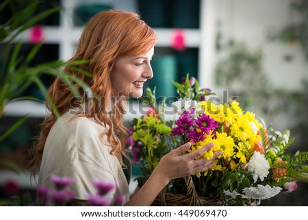 Happy female florist holding basket of flowers in the shop - stock photo